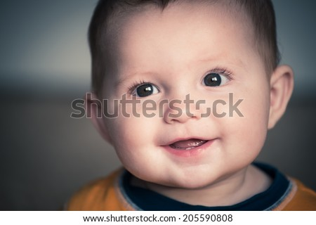 Close up portrait of cute happy baby smiling in vintage filtered image - stock photo