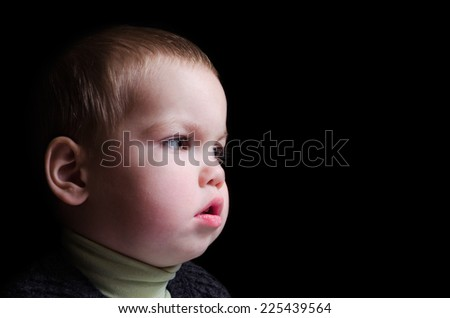 Close up portrait of cute little boy on black background  - stock photo