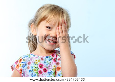 Close up portrait of Cute little girl closing one eye with hand against blue background.