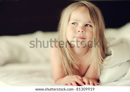 close-up portrait of cute little girl dreaming in bed - stock photo