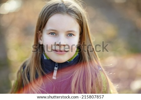 Close-up portrait of cute little girl in the autumn park. Portrait of red flare from sun