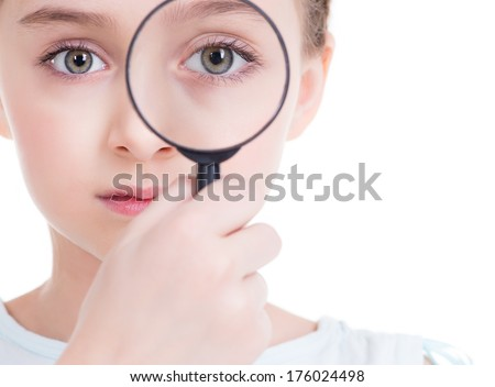 Close-up portrait of cute little girl looking through a magnifying glass - isolated on white.