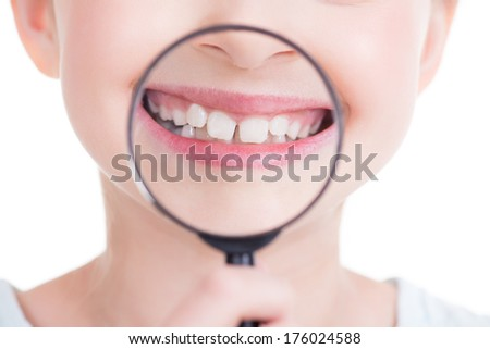 Close-up portrait of cute little girl showing teeth through a magnifying glass - isolated on white. - stock photo