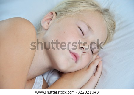 Close up portrait of cute little girl sleeping in her bed at home