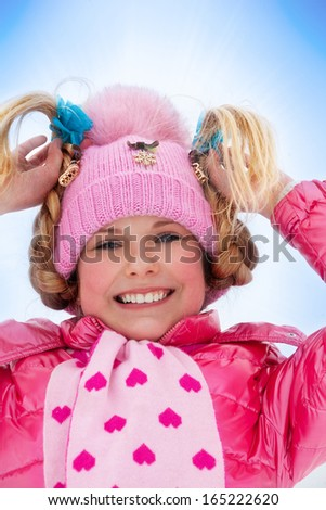 Close up portrait of cute smiling blond Caucasian girl in pink coat standing in snow - stock photo