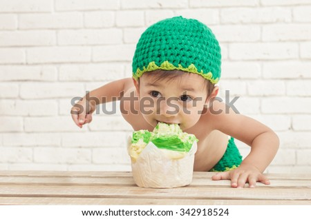close up portrait of cute toddler wearing green hat bite his sponge cake with white walls on background - stock photo