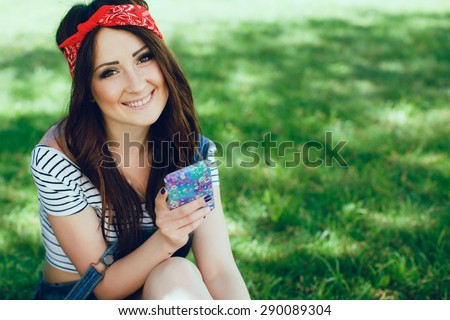 Close-up portrait of cute young brunette girl, sitting on the grass with smart phone. Wearing red bandana and striped top. Summertime. Copy space. - stock photo