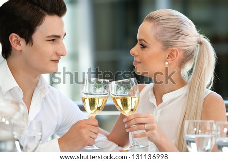 Close up portrait of cute young couple celebrating special moment with white wine. - stock photo