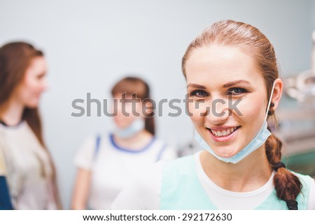 Close-up portrait of dentist smiling cheerfully with mask on her neck with patient and assistant talking on a background - stock photo