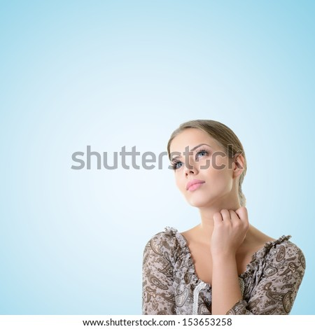 Close-up portrait of dreaming and planing girl looking up into the corner, over blue background with copyspace - stock photo