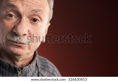 Close-up portrait of elderly man with a surprised expression on red background with copy-space