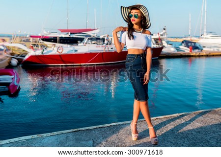 Close up  portrait of elegant glamour  asian lady in stylish  sunglasses posing in yacht club wearing straw hat, bright make up, hight crop top and jeans skirt , summer vacation mood.  - stock photo