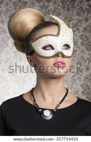 close-up portrait of elegant woman with classic blonde hair-style, necklace and cute decorated mask. Mysterious beautiful woman  - stock photo