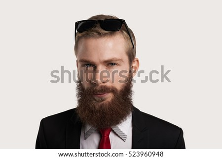 Close up portrait of european hipster guy with sun glasses, red tie, white shirt and black suit. Serious face of causian man. with big beard. Stylish look.
