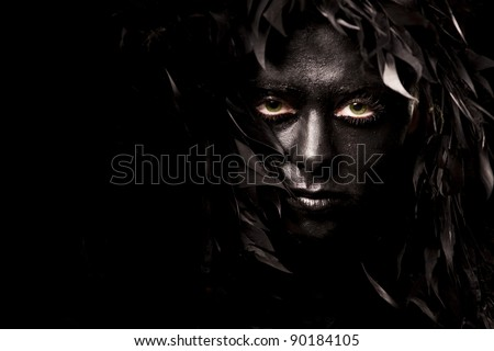 Close up portrait of evil spirit with green eyes, isolated on black - stock photo