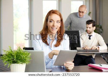 Close-up portrait of executive business woman holding digital tablet while working on project at office. Business meeting. - stock photo