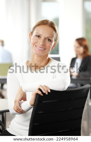 Close-up portrait of executive mature business woman sitting at office.