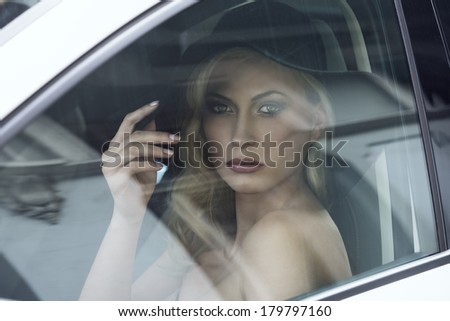 close-up portrait of fashion girl posing in white car with black hat, cute make-up, blonde hair and aristocratic style  - stock photo