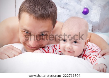 Close-up portrait of father and baby under the decorated Christmas tree - stock photo