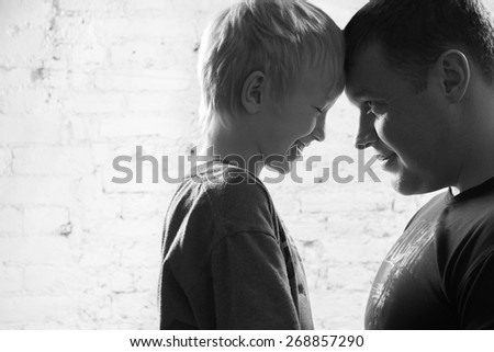 Close-up portrait of father and son - stock photo