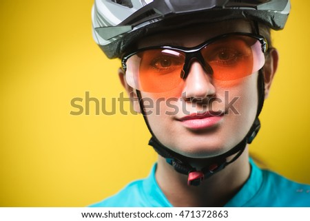 Close-up portrait of female cyclist wearing helmet and sport glasses