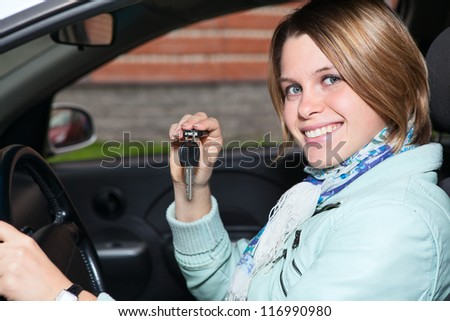 Close up portrait of female driver with car key in hand - stock photo