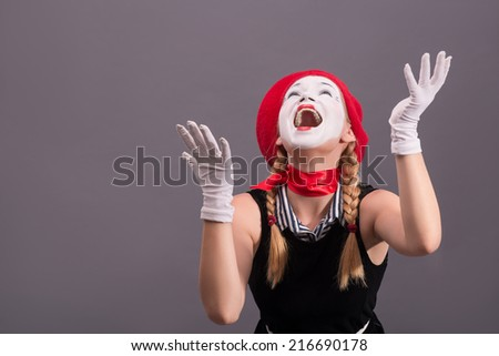 Close-up portrait of female mime with red hat and white face screaming and getting her hands up isolated on grey background with copy place - stock photo