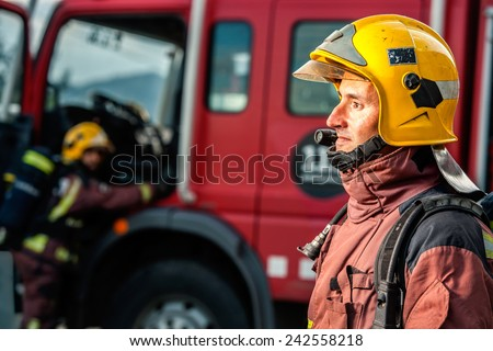 Close up portrait of Fireman staring at danger in front of fire truck. - stock photo