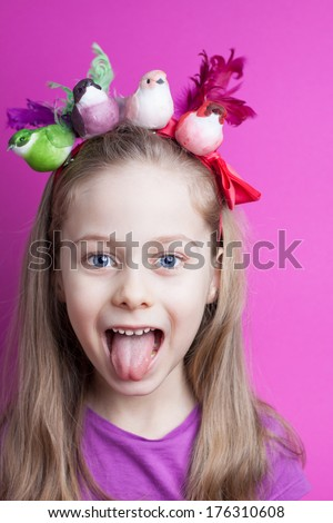 Close up portrait of five years old blond caucasian child girl with her tongue out and colorful birds on head - pastel purple background. Careless childhood, vacation and spring concept. - stock photo