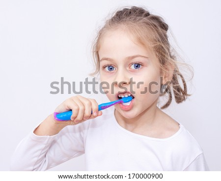Close up portrait of five years old caucasian blond child girl in pyjamas brushing teeth on a white background. Bedtime or morning - health, hygiene, dental care. - stock photo