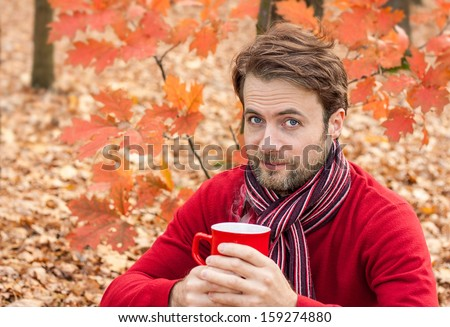 Close up portrait of forty years old caucasian man drinking hot tea or coffee outdoor in a park while autumn picnic - stock photo