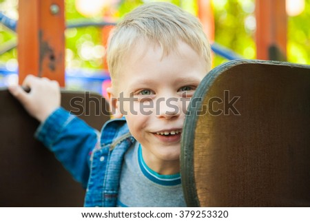 Close up portrait of funny smiling child face. 7 years old kid playing at children playground. Caucasian blond boy dressed in casual denim clothes. Happy kids playing on slide on spring or summer day.