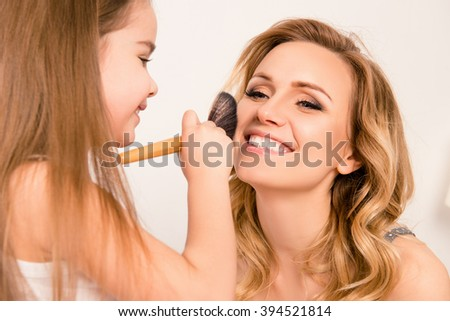 Close up portrait of girl doing makeup to her cheerful mom - stock photo
