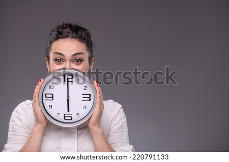 Close-up portrait of girl hiding her face with a big clock in her hands and looking at the camera, isolated on grey background with copy place concept of time management