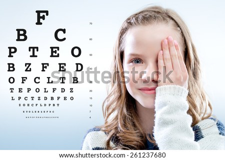 Close up portrait of Girl reviewing eye sight closing eye with hand.Test chart in background. - stock photo