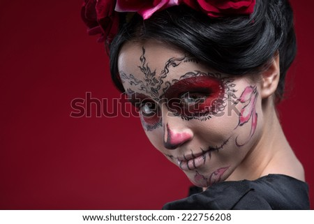 Close-up portrait of girl with Calaveras makeup and a red flower in her black hair looking at you and lightly smiling isolated on red background with copy place - stock photo