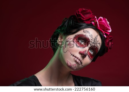 Close-up portrait of girl with Calaveras makeup and three red flowers in her black hair looking aside with a light smile and thinking about something isolated on red background with copy place - stock photo