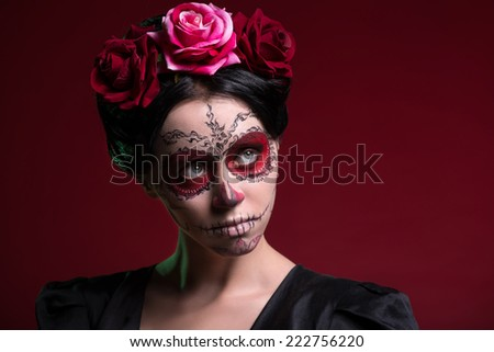 Close-up portrait of girl with Calaveras makeup and three red flowers in her black hair seriously looking aside isolated on red background with copy place - stock photo