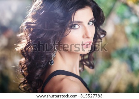 Close-up portrait of gorgeous brunette woman with perfect makeup and hairstyle
