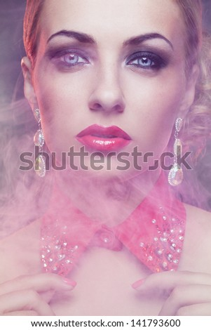 Close-up portrait of gorgeous woman in fog with bright make-up wearing red collar covered with crystals - stock photo