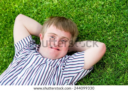 Close up portrait of handicapped boy laying with hands under head on green grass. - stock photo