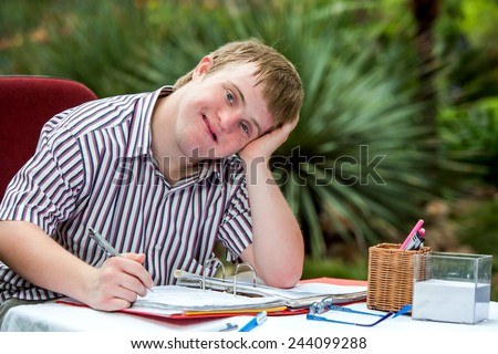 Close up portrait of Handicapped student resting on hand at desk in garden. - stock photo