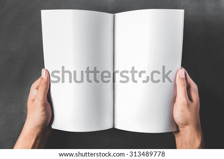close up portrait of hands holding an open book with blank page on dark background - stock photo