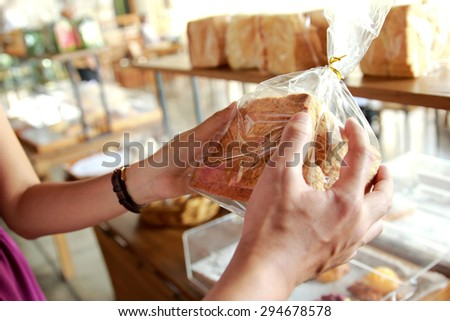 close up portrait of hands of couple holding a pack of bread - stock photo