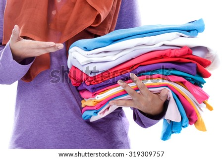 close up portrait of hands presenting clean and tidy folded clothes after ironing