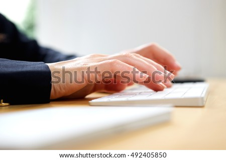 Close up portrait of hands typing on keyboard