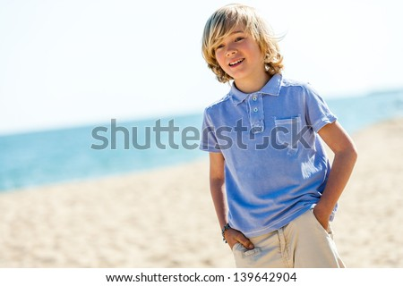 Close up portrait of handsome blond boy standing on beach.