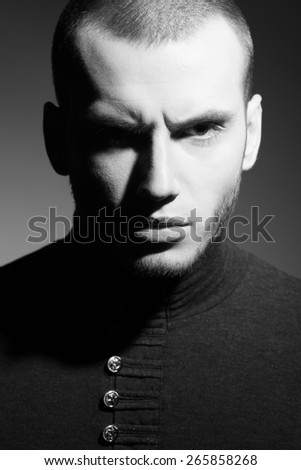 Close up portrait of handsome brutal young model with short hair and bristle on face posing over dark gray background. Hipster style. Black and white studio shot - stock photo