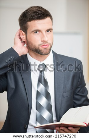 Close-up portrait of handsome businessman in office interior holding a red notebook in his hands touching his head looking at the camera and thinking or making some decision - stock photo