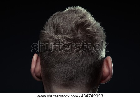 Close up portrait of handsome charismatic man's back posing over dark gray background. Modern stylish haircut. Studio shot
